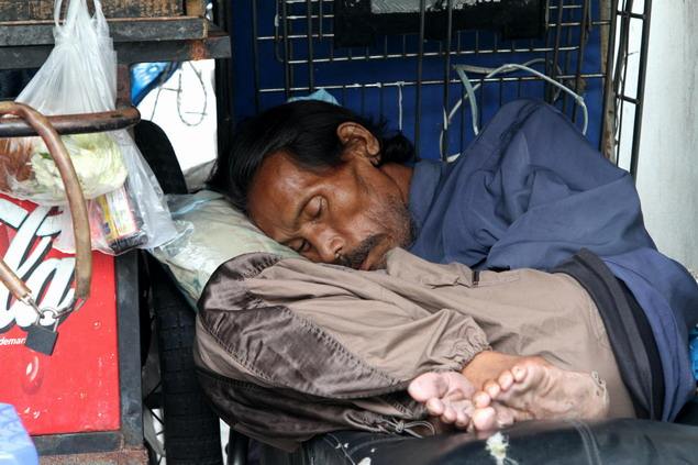 A man is tucked up at a street corner as the temperature in Bangkok dropped to 17 degrees Celsius yesterday.