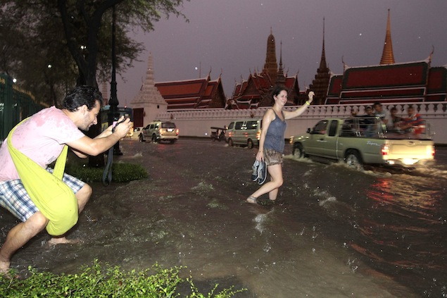 Foreign tourist poses with floodwaters in front of the Temple of the Emerald Buddha as the water level keeps rising.