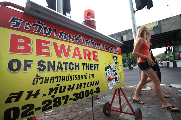 Thung Mahamek police have installed this board warning passersby to be aware of bag snatchers at the junction of Sathon Road and Witthayu Road in Bangkok. Photo by Patipat Janthong.