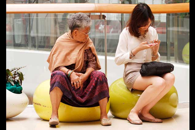 An elderly lady wearing a traditional pa toong peaks at a smartphone in an office worker's hand at Central Ladprao shopping centre. The Central Administrative Court will hand down a ruling on whether next week's auction of the 3G wireless spectrum can go ahead. Photo by Thiti Wannamontha.