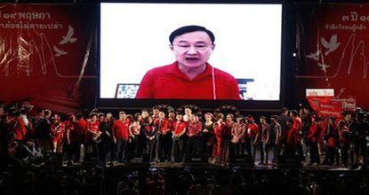 Fugitive former Prime Minister Thaksin Shinawatra addresses red-shirt supporters via Skype on May 19, 2013.