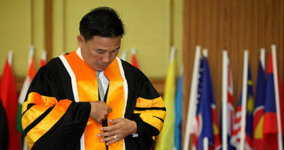 A grantee for an honorary certificate of the Universal Ministries of Thailand takes off his gown ordered by officials as it is the same as the one used by the World Peace University.