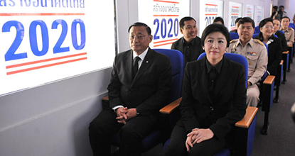 Prime Minister Yingluck Shinawatra sits with other officials in a mockup of a high-speed train carriage at Khon Kaen University, before explaining the 2-trillion baht loan plan  in October 2013