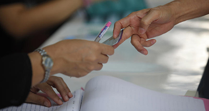 A voter hands an ID to an election official for checking at a polling unit in Bung Kum district in Bangkok on Sunday.