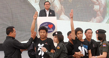 Khon Kaen students in t-shirts with an anti-coup message give the anti-coup salute in front of Prime Minister Prayut Chan-o-cha's stage in Khon Kaen.