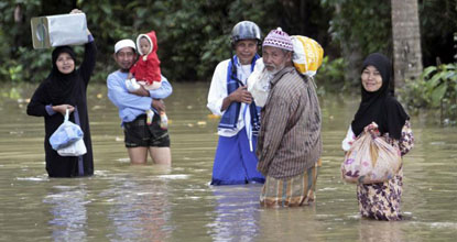 People wade through flood water inundating their community  in Pattani on Friday (Reuters photo)