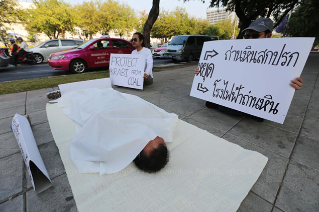 A demonstrator poses as a dead man in front of the Tourism and Sports Ministry as part of a campaign against a coal-fired power plant planned in Nua Khlong district in Krabi, which, the protesters say, could damage tourism in the province. — Pattarachai Prechapanich