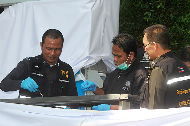 Forensic police officers at the bomb scene in front of the Siam Paragon shopping centre collect samples for use as evidence on  Monday. (Photo by Thanarak Khunton)
