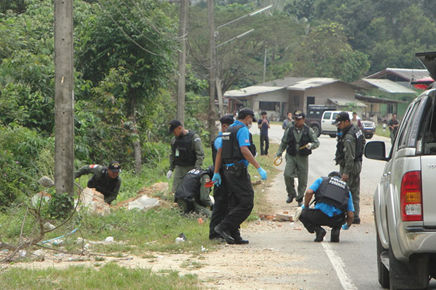 Bomb disposal officers inspect a blast site in Chanae district of Narathiwat on Feb 5. The home-made bomb, believed to target police, went off shortly after one of two police vehicles past the site. (Photo by Waedao Harai)