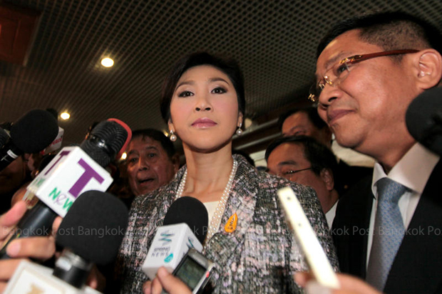 Former prime minister Yingluck Shinawatra talks to reporters last month after arriving at parliament to deliver her closing statement on the rice scheme. (Photo by Chanat Katanyu)
