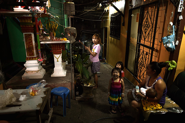 A woman offers prayers to a spirit house in a slum area in downtown Bangkok. Thailand's spiralling household debt is just one of a number of troubling malaises afflicting a struggling economy that shows little sign of improvement despite the government's promises to revive the country's economic health. (AFP photo)