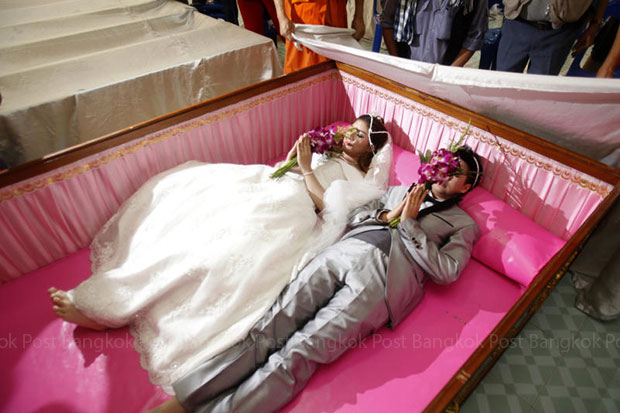 A bride and groom lie in a pink coffin in a wedding ceremony organised by Wat Ta Kien in Bang Kruay district in Nonthaburi on Saturday. (Photo by Pattarapong Chatpattarasill)