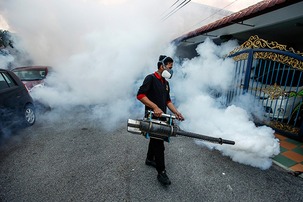 A Malaysian Health Department staff member uses a nebuliser to spray insecticide in order to control the mosquito population in Kuala Lumpur on Jan 22. (EPA photo)