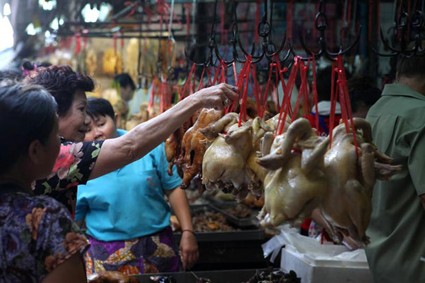 A woman is choosing a chicken in preparing for the Chinese New Year in Yaowarat on Tuesday. (Bangkok Post photo)