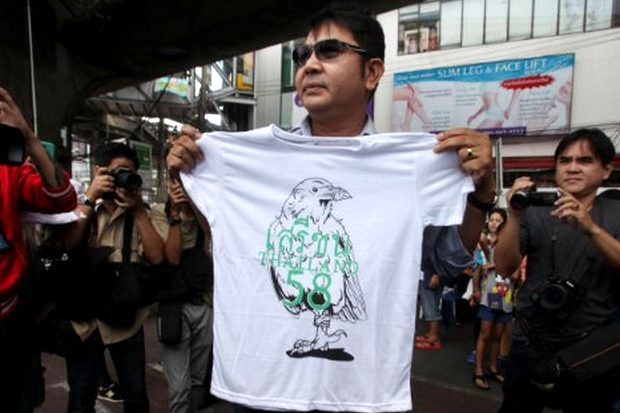 Democracy advocate Akharadet Nunchan hands out T-shirts with a gagged pigeon to passersby as part of his group's anti-coup campaign near Victory Monument. Police quickly escorted him from the scene. (Photo by Pornprom Satrabhaya)