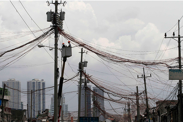 Workers standing in a hydraulic lift examine illegal electrical connections during a routine check on utility poles along a road in a slum area in Manila. The Philippines said Wednesday it would end Chinese technical involvement in running the country's power grid. (Reuters photo)