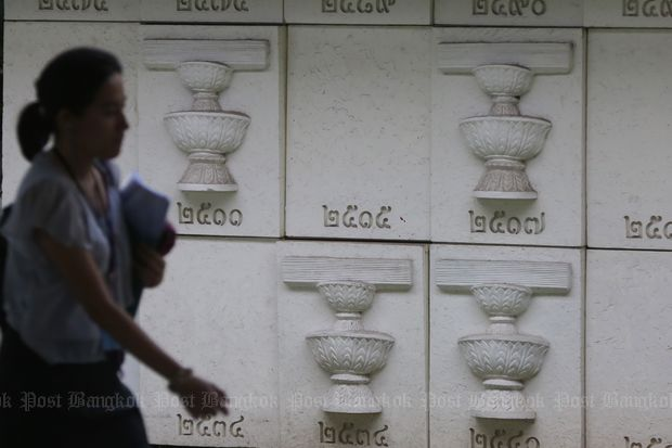 A woman walks past a wall with bas-relief engravings of past constitutions at Thai Parliament Museum at Parliament in Bangkok. (Bangkok Post file photo)