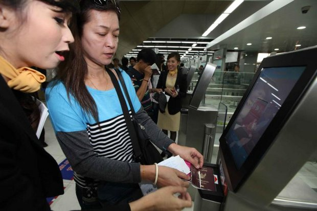 A Thai arrival gets some help from a receptionist in scanning her passport, leaving immigration officers free to handle more complex problems. (Photo by Somchai Poomlard)