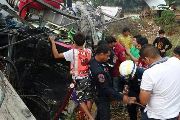Police examine the wreckage of the tour bus after it crashed into a roadside power pole and overturned in Wang Thong district of Phitsanulok early on March 3. (Photo by Chinnawat Singha)