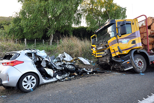 """A car and a logging truck sit damaged after they collided head-on Feb 17 near Tokoroa, New Zealand. Three Americans were killed when their car crashed into the logging truck. Tourists driving on the wrong side of the road have prompted some New Zealanders to become """"road vigilantes,"""" authorities said. (AP photo)"""