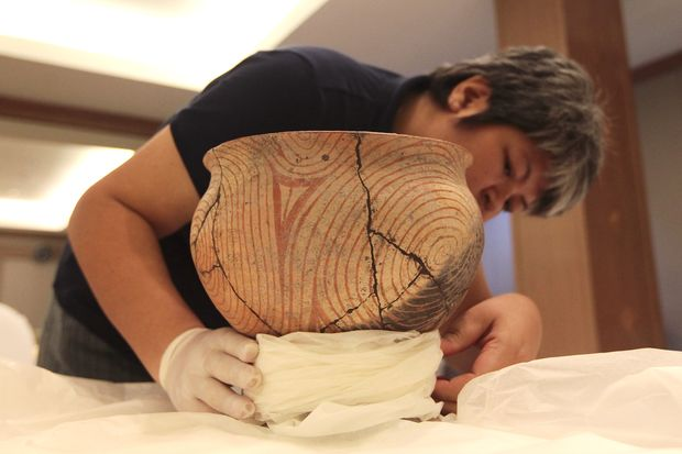 A National Museum employee in Bangkok tends to a bowl from Ban Chiang, a Unesco World Heritage Site in northeastern Thailand. (File photo by Patipat Janthong)