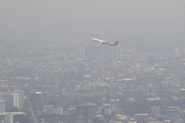 Haze hangs over Chiang Mai as a plane heads out for clearer skies. (EPA photo)