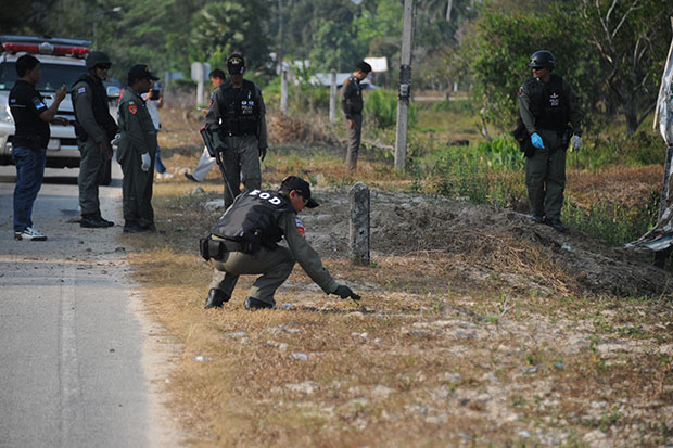 Bomb disposal officers inspect a blast site in Cho Airong district of Narathiwat on Saturday. Two police in a pickup truck survived when the home-made bomb went off. (Photo by Wadaeo Harai)