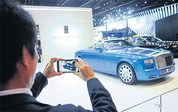 An exhibitor takes a picture of a Rolls-Royce Phantom Drophead Coupe at the 36th Bangkok International Motor Show. The 12-day event runs until April 5 at Impact Muang Thong Thani and is expected to attract 1.5 million visitors.(Photo by Wichan Charoenkiartpakun)