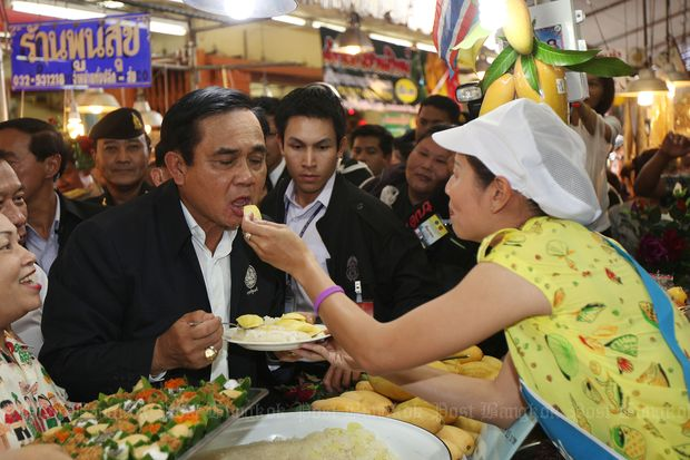 Prime Minister Prayut Chan-o-cha takes a bite of sticky rice with mango at the Chatchai Market in Hua Hin on Friday. (Photos by Thiti Wannamontha)