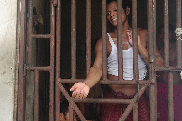 In this Nov 22 image, Kyaw Naing, a slave from Myanmar, talks to a security guard through the bars of a cell at the compound of a fishing company in Benjina, Indonesia. (AP photo)