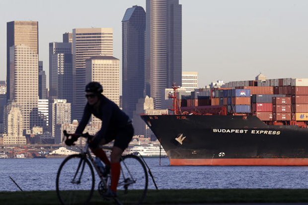 A bicyclist rides in view of a loaded container ship anchored in Elliott Bay near downtown Seattle on Nov 17, 2014. The US Commerce Department releases international trade data for February on Thursday. (AP photo)