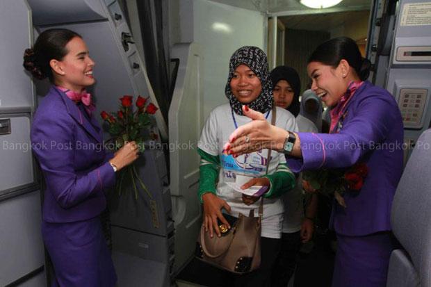 Thai Airways International crewmembers direct passengers into the aircraft. (Bangkok Post file photo)