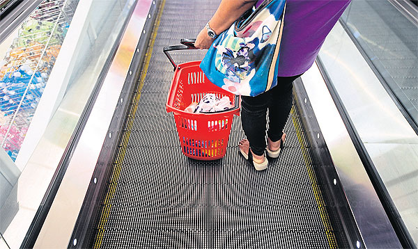 A shopper uses an escalator at a supermarket in Bangkok. Analysts expect Thailand's consumer spending will start improving markedly in the second half of this year after months of stagnation. (Photo by Patipat Janthong)