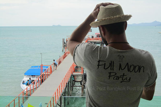 A full-moon party-goer waits on Koh Samui to board a high-speed boat to Koh Phangan in Surat Thani province. (File photo by Boonsong Kositchotethana)