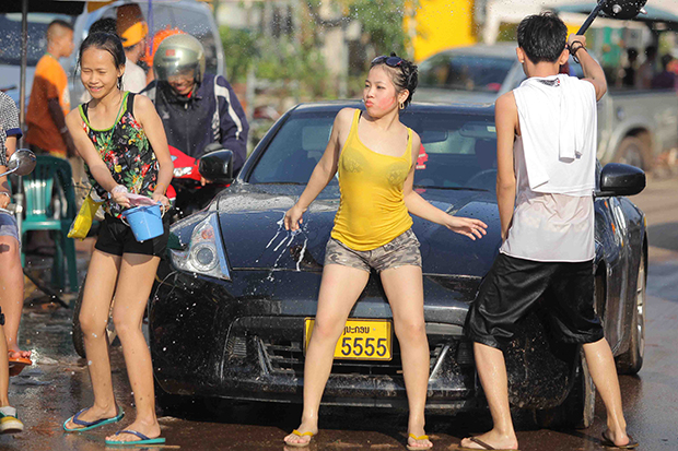 "Lao teenagers in 2012 a splash in Vientiane during the Lao New Year, but officials there this year are cutting into the fun, closing entertainment venues early and banning ""skimpy"" clothing. (Photo by Pattanapong Hirunard)"