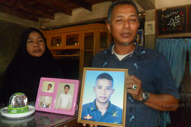 Suraya and Sakariya Sameang show the last picture taken of their son Kholid, in the pink frame, at their house in Thung Yang Daeng district in Pattani province. (Photo by Abdulloh Benjakat)