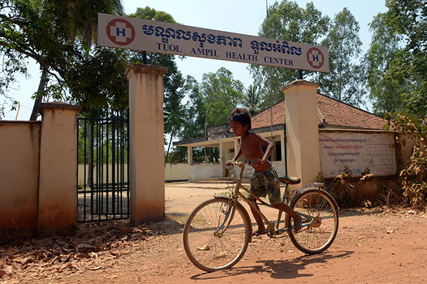 A Cambodian child rides his bicycle past a health centre at a village in Kampong Speu province. About 70% of Cambodians seek healthcare from the private sector -- including from pharmacies, illegal doctors or traditional healers, known as khru khmer -- according to a 2012 survey by the World Health Organization. (AFP photo)