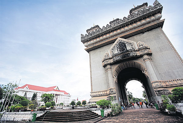 Tourists walk under Patuxai, the Gate of Victory, a landmark in Vientiane. Concerns over economic overdependence on China have prompted Laos to explore its options in cooperating with  other countries such as Japan, South Korea and the United States. file photo