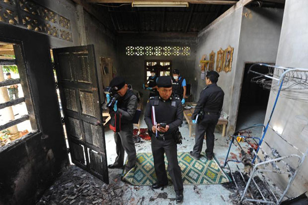 Police inspect one of the two houses where four people were murdered, two of them burned, by suspected armed insurgents at Narathiwat's Sukhirin district on Sunday. (AFP photo)