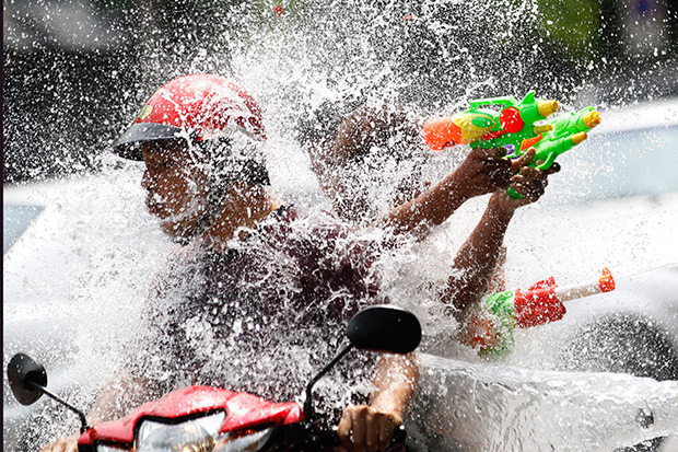 People riding on a motorbike react as a boy splashes water on them during a Songkran celebration in Bangkok Monday. Water being thrown at motorbikes is a leading cause of accidents during the period. (AP photo)