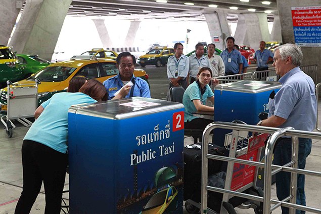 A foreigner waits to get a taxi queue ticket at Suvarnabhumi Airport. (Photo by Somchai Poomlard)