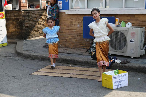 Two girls perform Thai dance to fund their education at Chatuchak weekend market in February 2015. (Bangkok Post file photo)