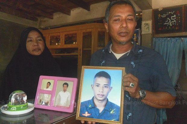 The last photo of their son Kholid before he was killed by paramilitary rangers is shown by Suraya and Sakariya Sameang at their Thung Yang Daeng home. The parents pursued a claim of wrongful death but the army now is transferring those responsible for the unlawful killing. (Photos by Abdulloh Benjakat)