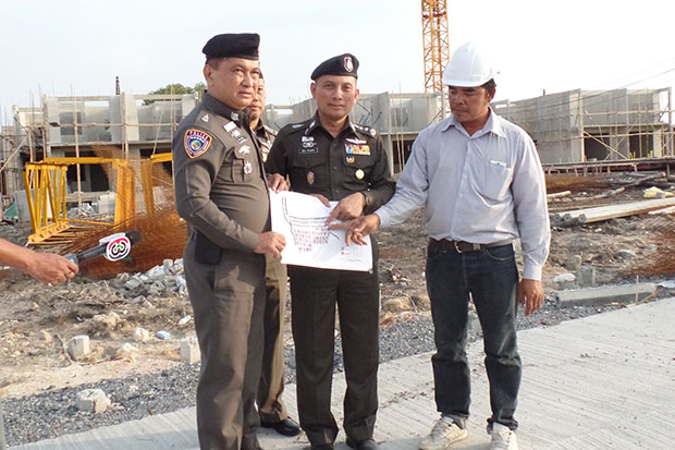 Assistant national police chief Suwira Songmeta (centre) leads a team of police to inspect and seize 100 housing units at the Bangkok Marina Resort & Spa project in Samut Prakan on April 23. (Photo by Sutthiwit Chayutworakan)