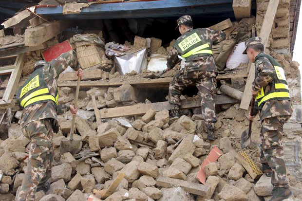 Chinese police search ruins of buildings damaged by the 7.9-magnitude earthquake that hit Nepal on Saturday, in Gyirong county, Tibet Autonomous Region, China, on April 26, 2015. (Reuters photo)