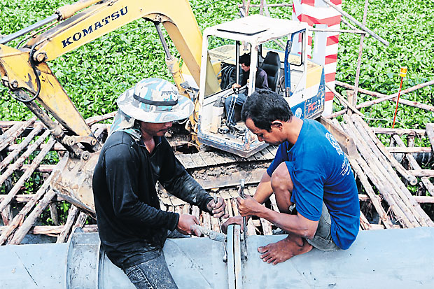 Workers dismantle a water pipe along Khlong 4 Road to make way for a road expansion project in Pathum Thani. The government is promoting workplace safety and better welfare for workers to mark Labour Day today. APICHIT JINAKUL