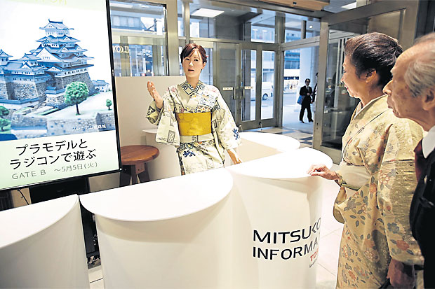 Replacing humans, a kimono-clad android robot named Aiko Chihira greets visitors at the reception desk in a department store in