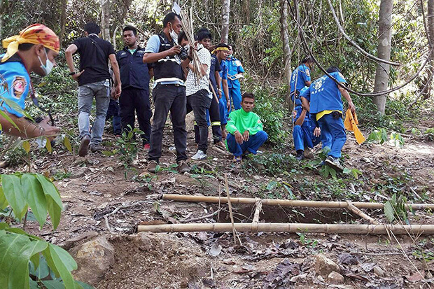 Rescue workers and forensic officials inspect the site of a mass grave uncovered at an abandoned jungle camp in the Sadao district of Songkhla province bordering Malaysia on May 1. (AFP photo)