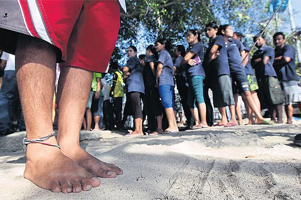 A migrant worker presses his foot into the sand before taking a DNA test, while others queue for similar tests. All male migrant workers on Koh Tao were considered suspects in the murder of two British tourists and required to take footprint and DNA tests.(Photo by Thiti Wannamontha)