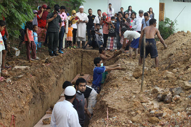 Rescue workers bury coffins containing bodies recovered from a mass grave in Songkhla's Sadao district. They were interred at a local Muslim cemetery in Songkhla's Hat Yai district. (Bangkok Post file photo)